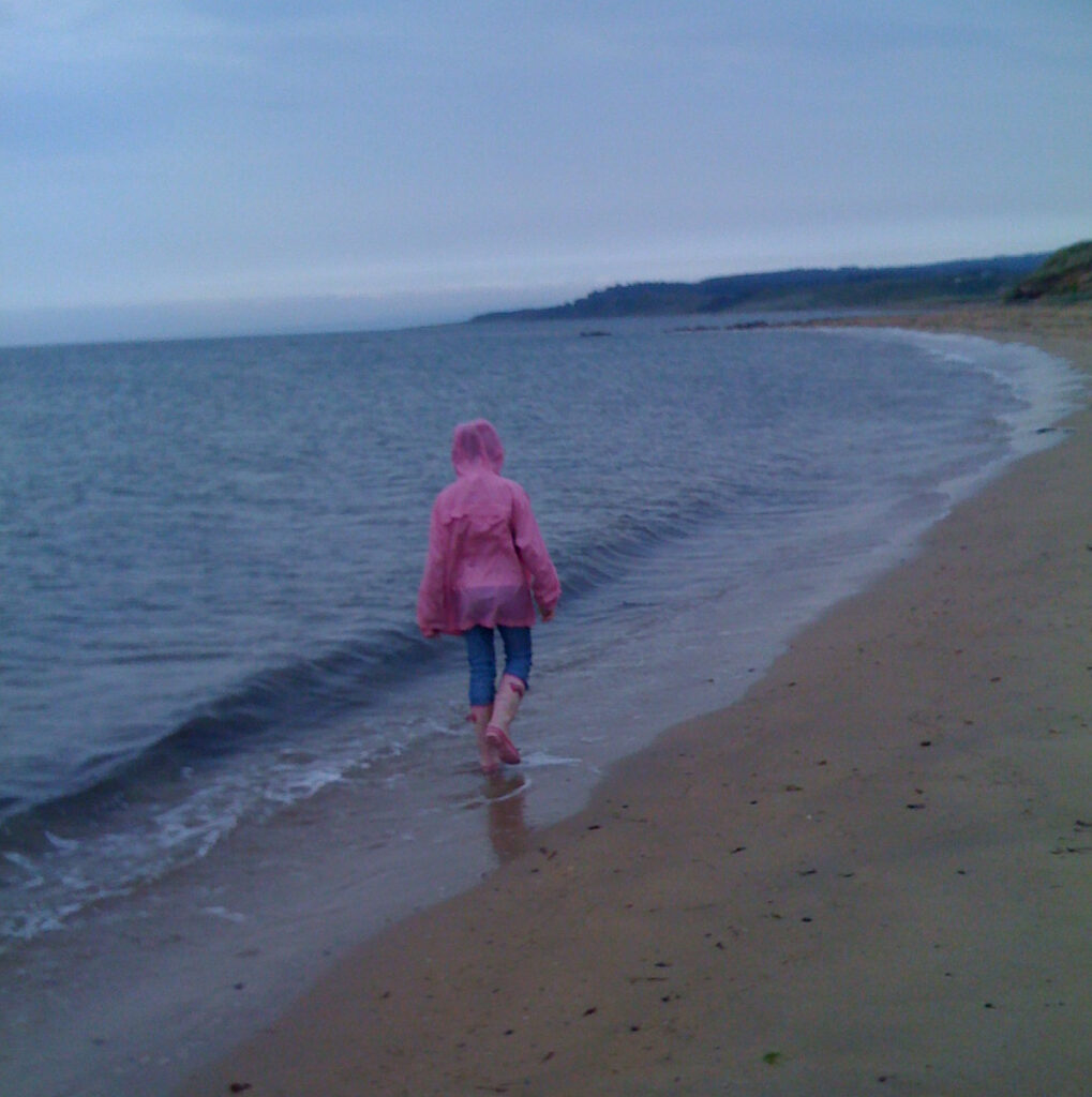 A young person dressed in a pink waterproof and wellies walking along the beach in the wash of the waves.