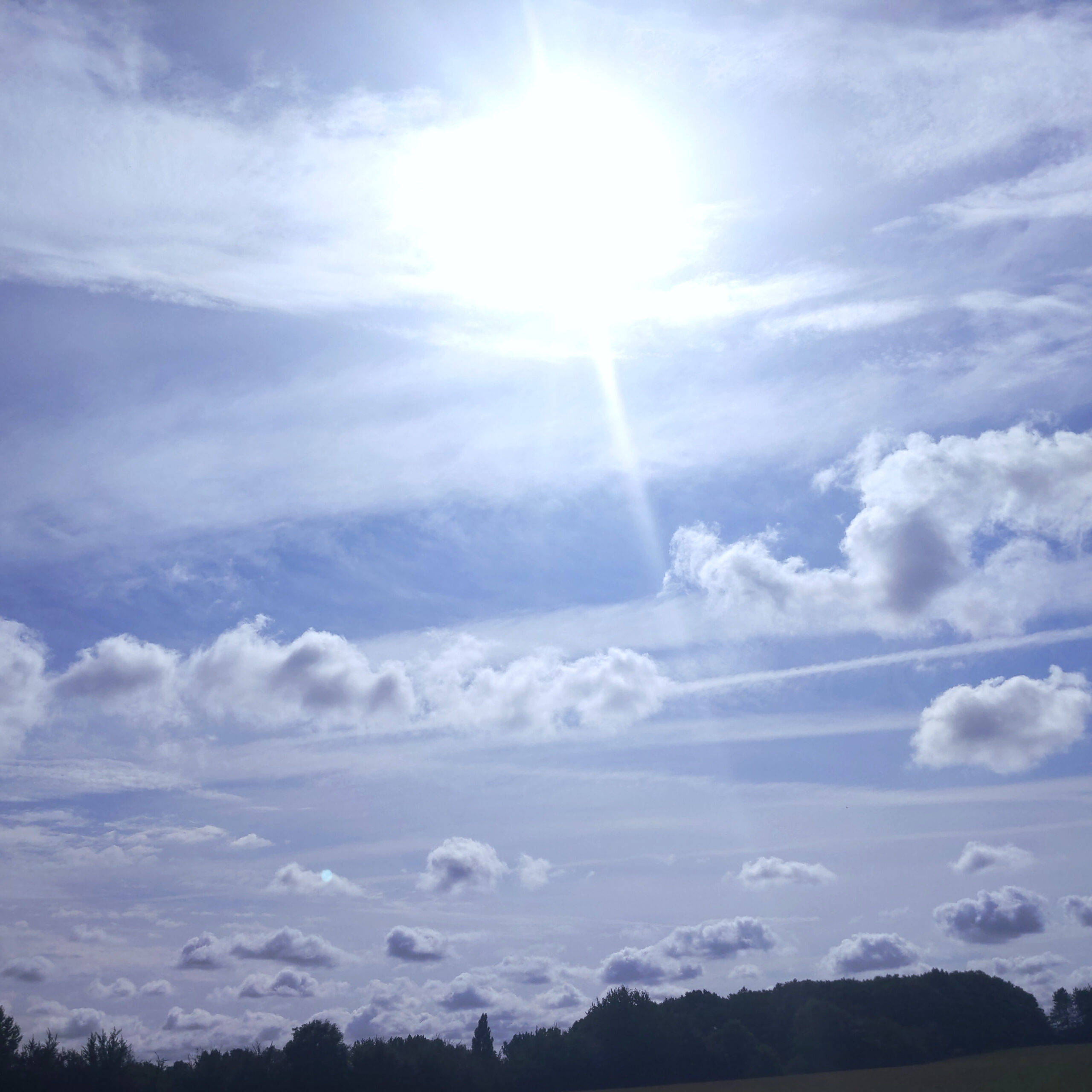 An intense picture of a summer sky. The sun and the clouds lie hazy across the majority of the photo.